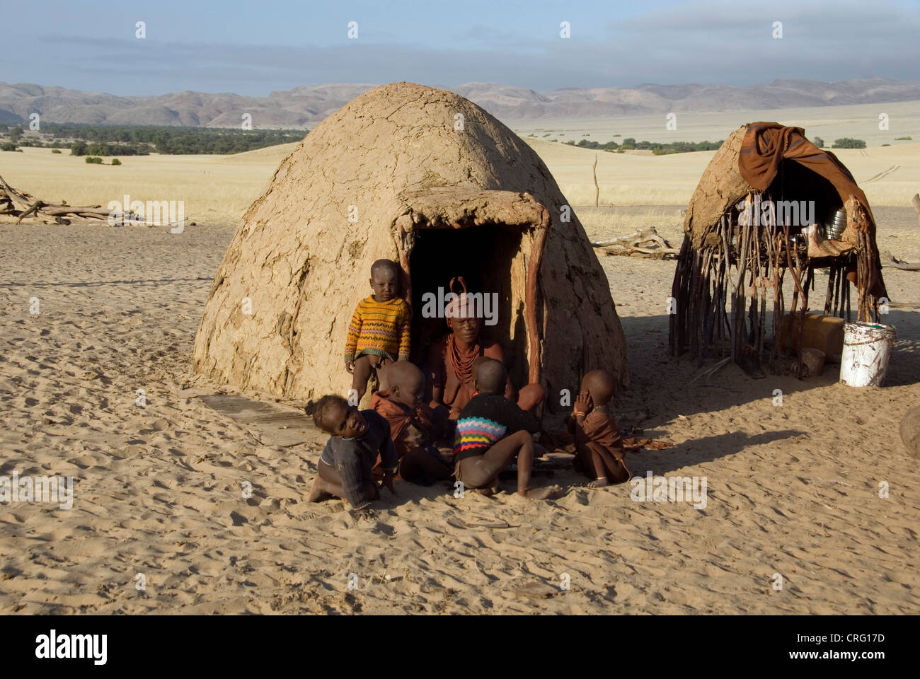 traditional Village of Purros, Himba woman with children in front of a hut, Namibia, Purros - Stock Image