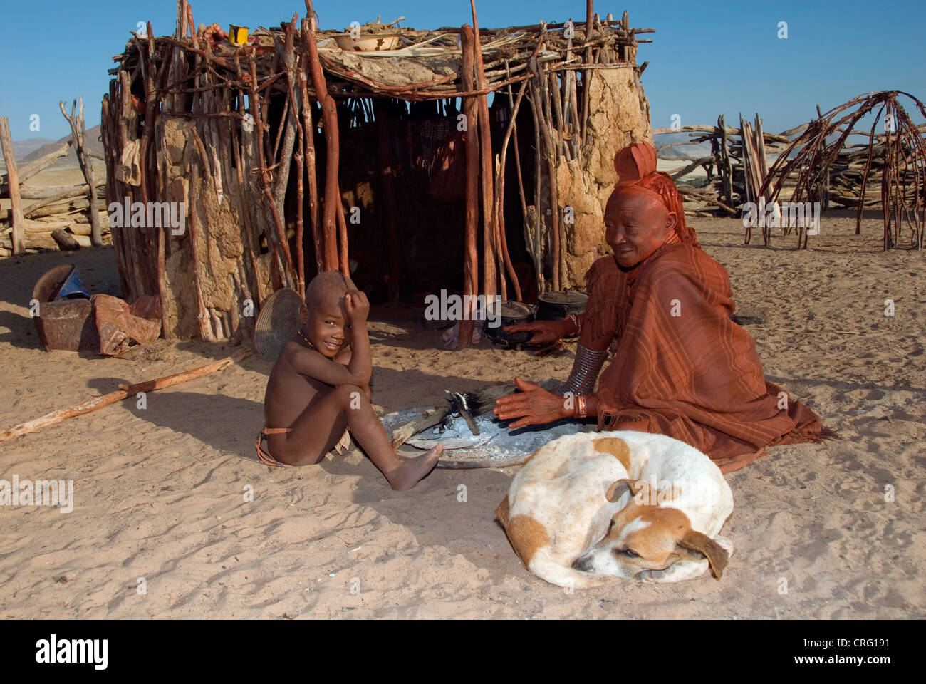 traditional Village of Purros, Himba woman with boy and dog in front of a hut, Namibia, Purros - Stock Image