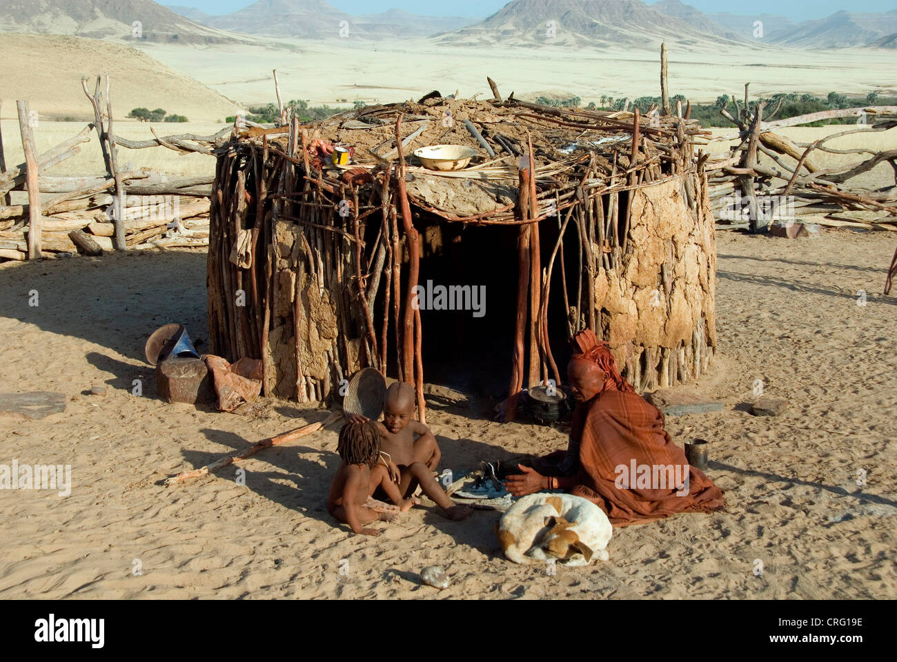 traditional Village of Purros, Himba woman with children and dog in front of a hut, Namibia, Purros - Stock Image