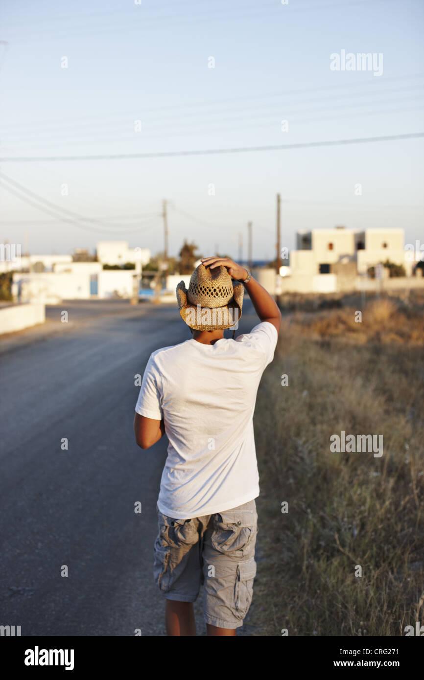 Man walking on rural road - Stock Image