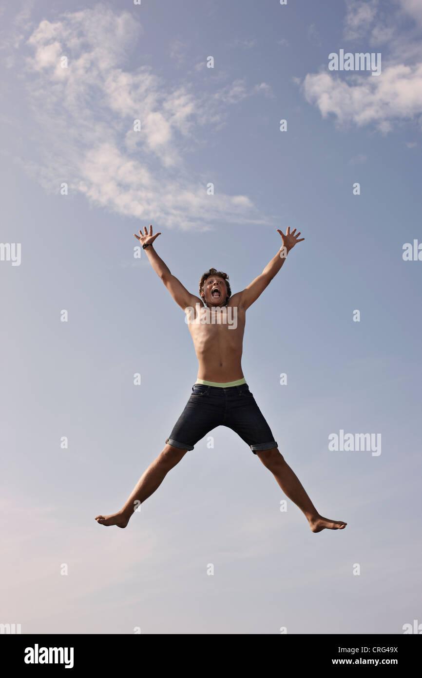 Teenage boy posing in mid-air - Stock Image