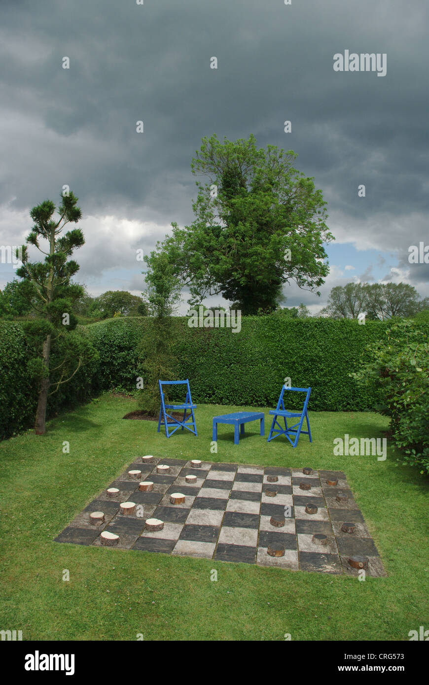Giant draughts game, made of wood, set into a lawn in an English Country garden - Stock Image