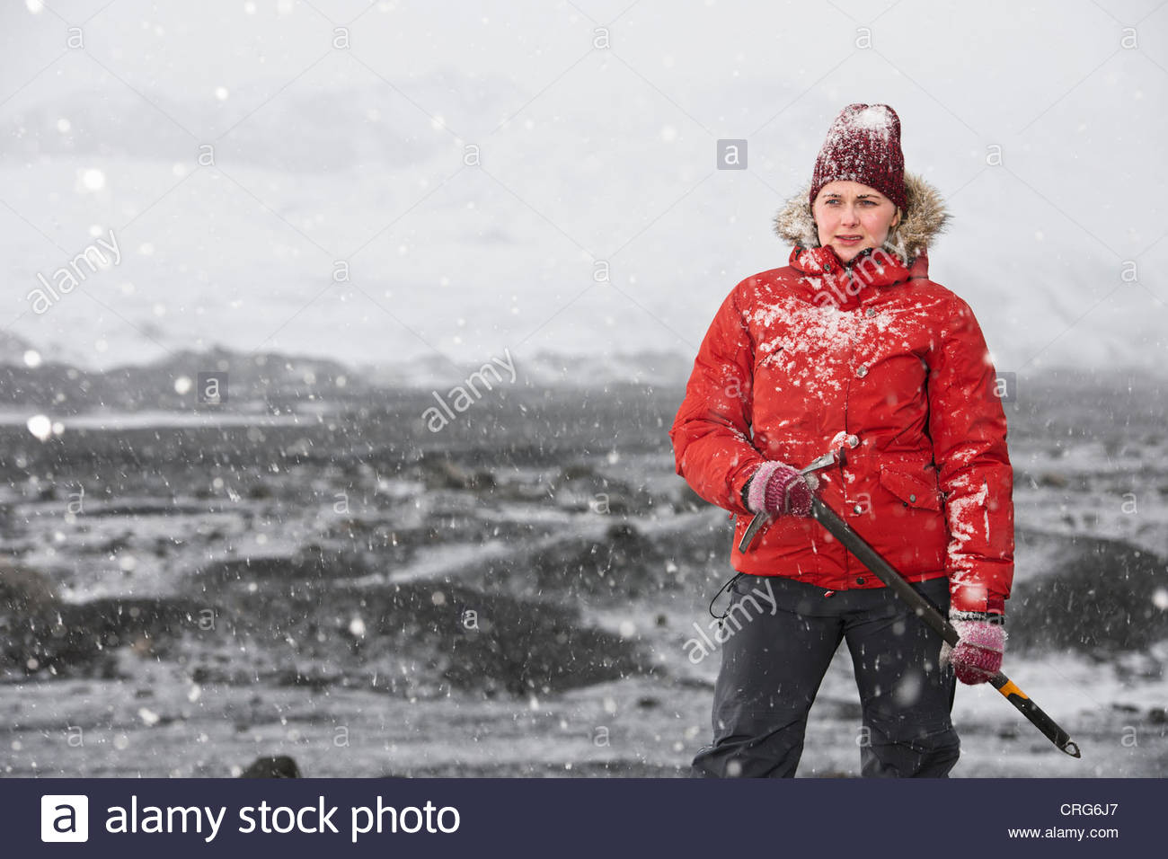 Hiker carrying pickax in snow - Stock Image