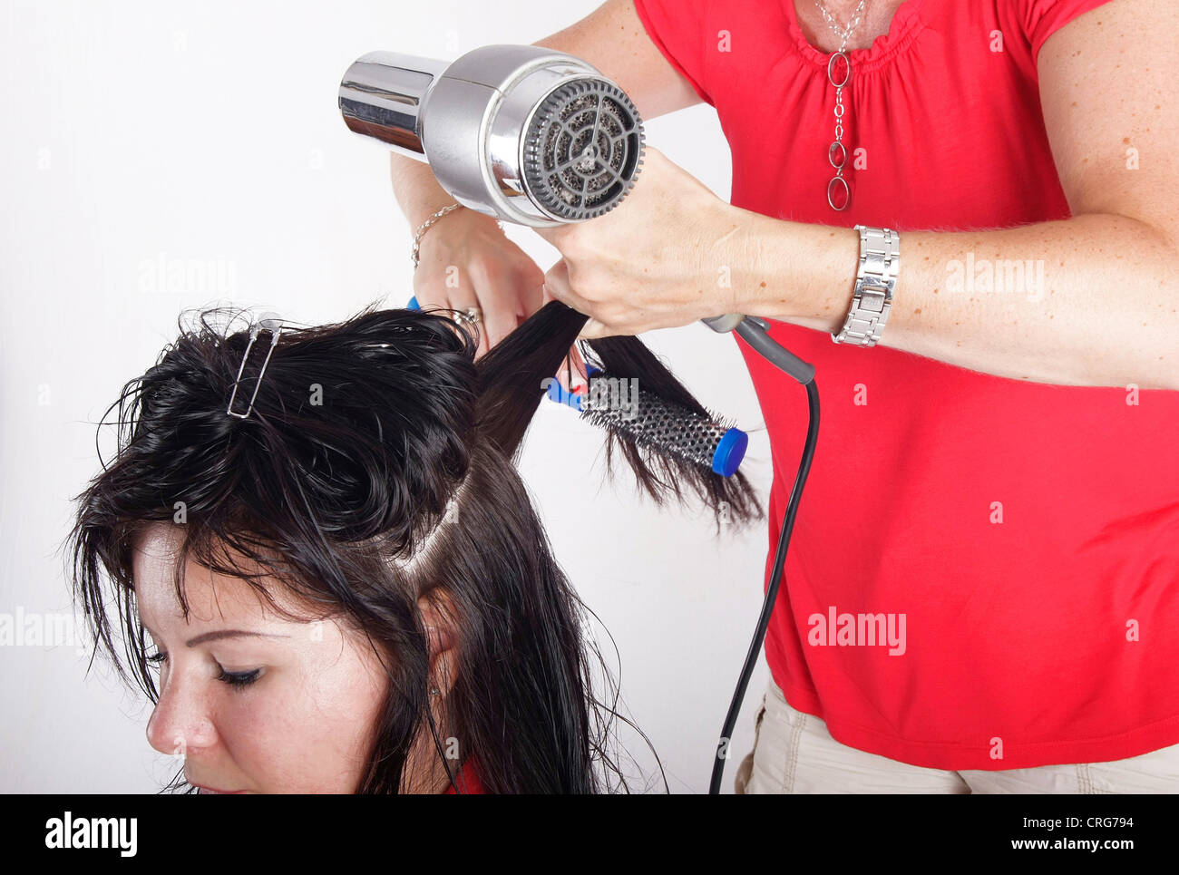 woman at hairdresser, drying and styling the wet hair - Stock Image