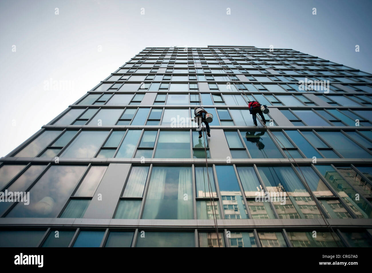 Window washers work, dangling from a glass-sided building high above third avenue in the East Village in Manhattan. - Stock Image