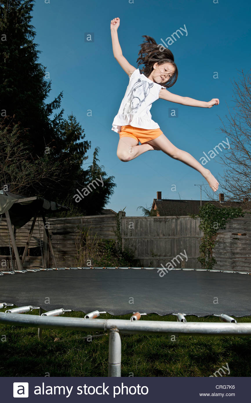 Smiling girl jumping on trampoline Stock Photo