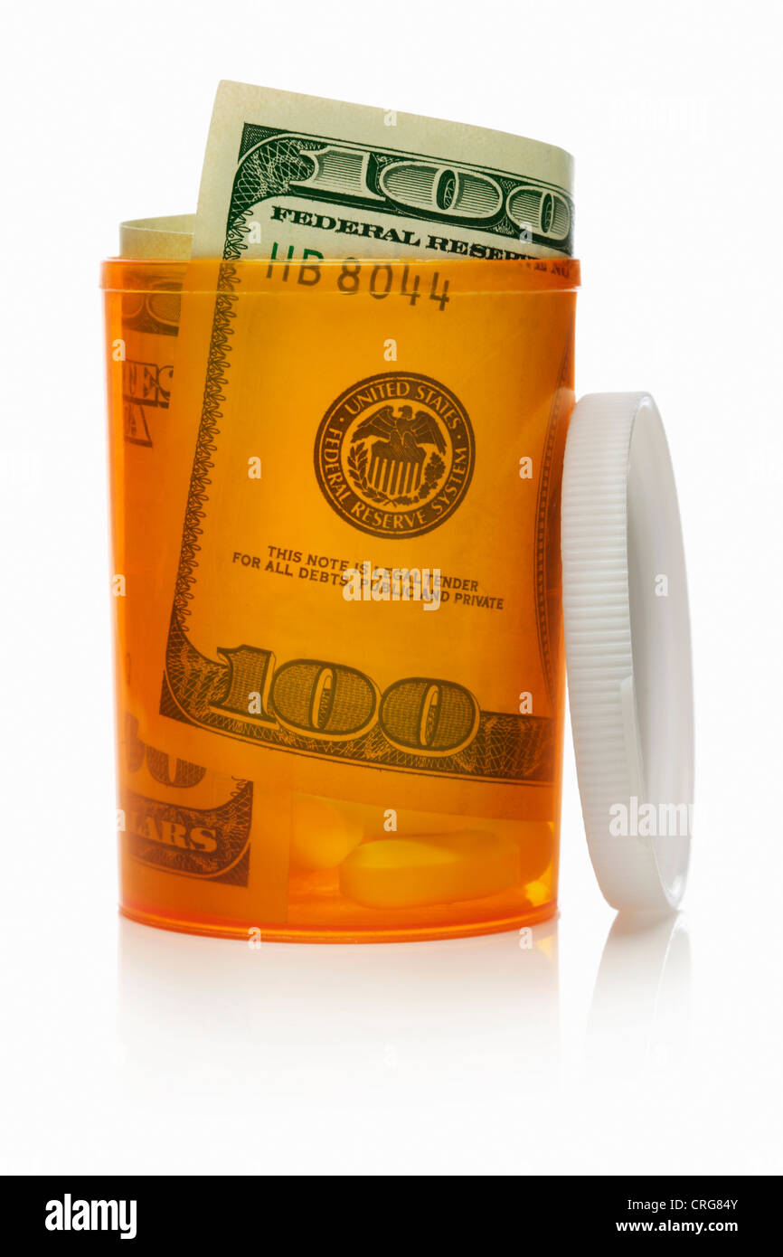 Close up of U.S. dollars in pill bottle Stock Photo