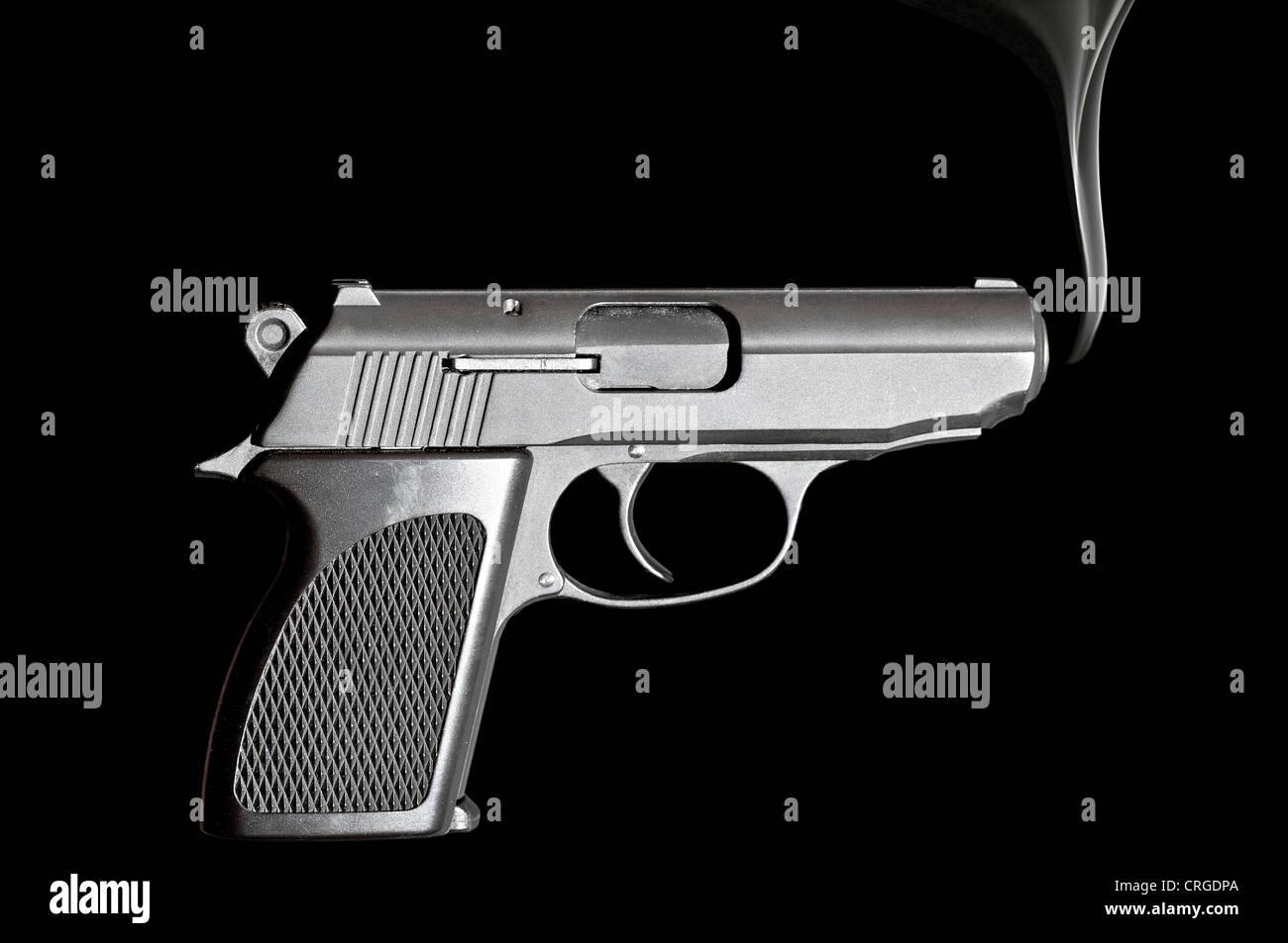 Handgun with smoke emerging from it - Stock Image