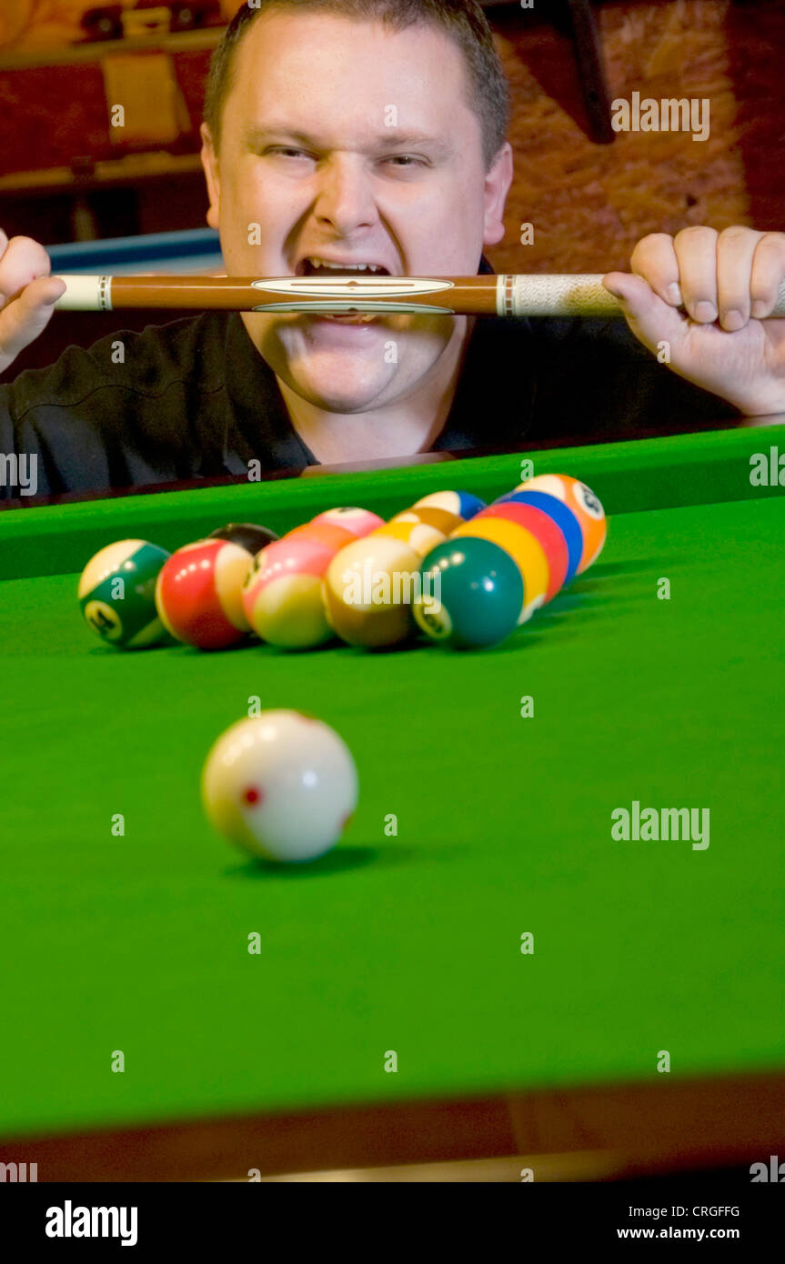 billiard player biting in cue stick - Stock Image