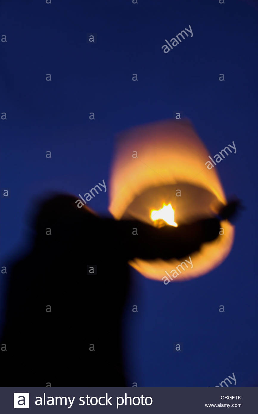 Man sending off up in to the sky a paper Thai lantern at night. UK. - Stock Image