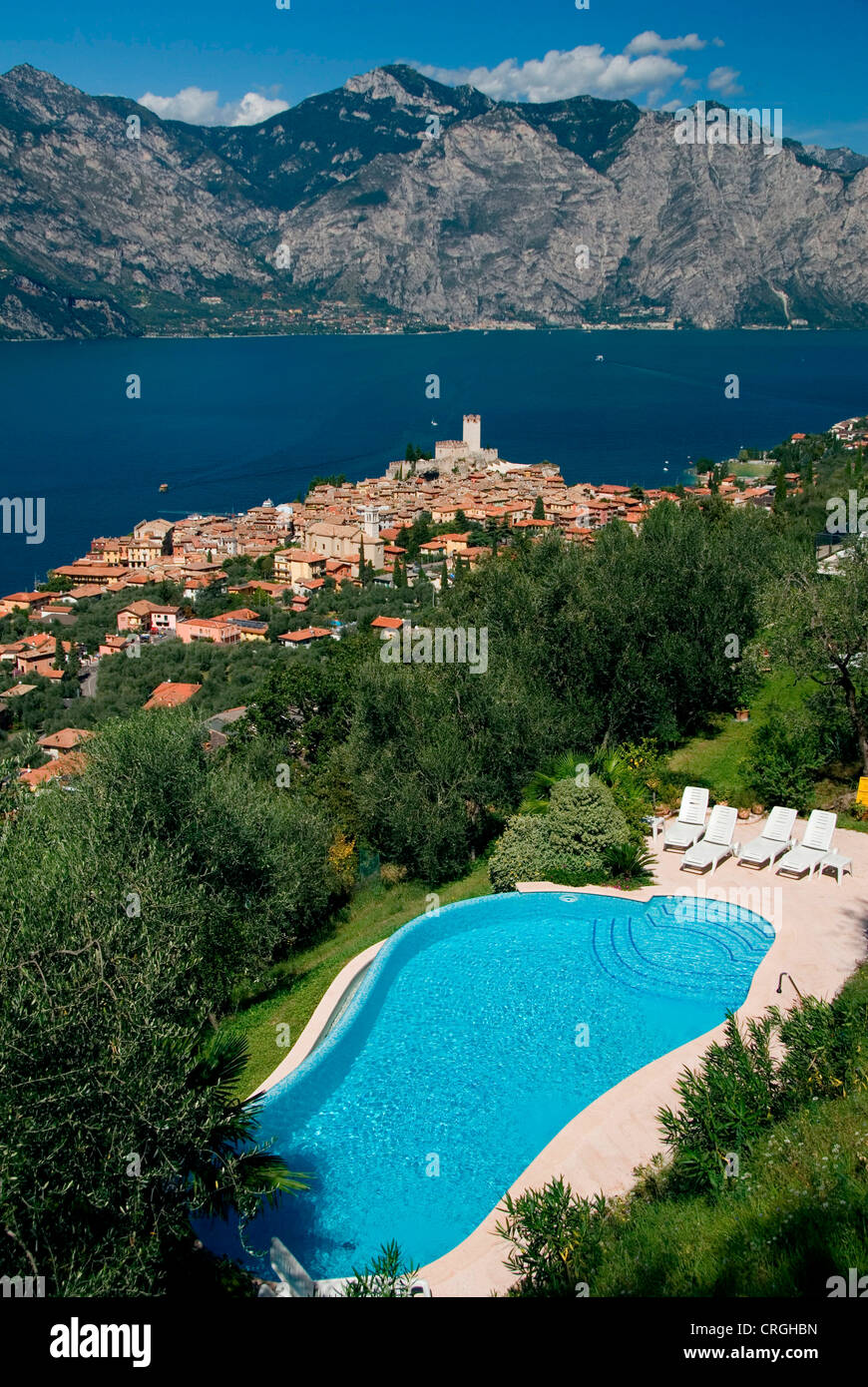 view on the village, Scaliger castle and Lake Garda, with a swimming pool in the foreground, Italy, Veneto, Malcesine Stock Photo