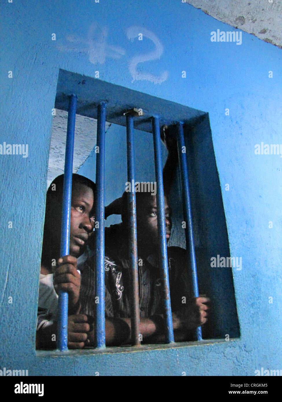 detainees behind bars of a window in run-down predetention cell (garde � vue) at police station, commissariat of - Stock Image