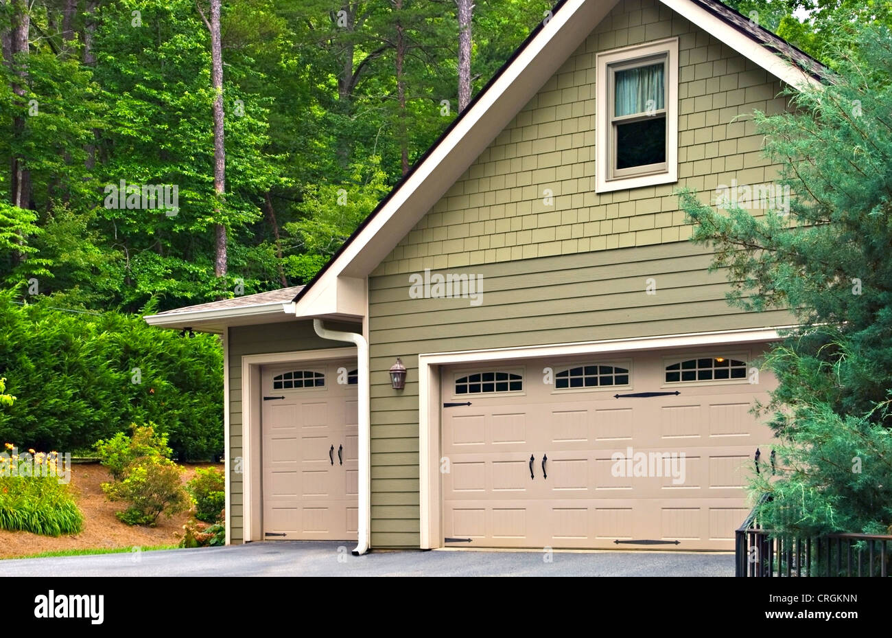 Garage doors on a modern house. Double doors with windows on one side and an off-set single beside it. - Stock Image