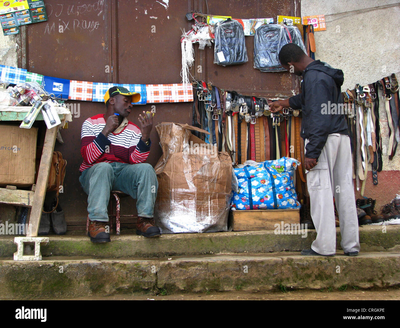 young man sitting at his general merchandise sales booth shaving dry, another , Haiti, Province de l'Ouest, - Stock Image