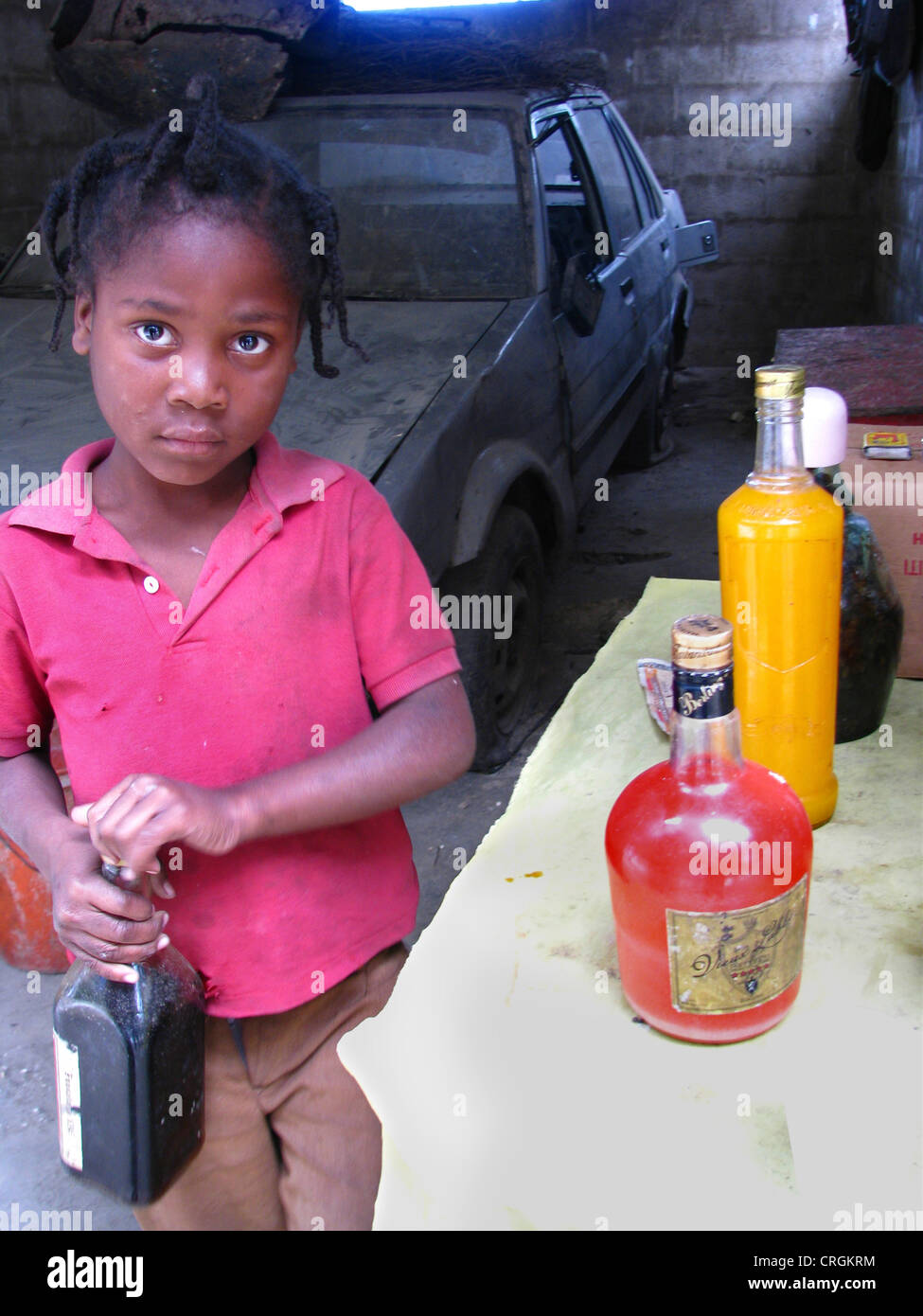 Young boy in garage selling locally produced alcohol to bypassers, Haiti, Province de l'Ouest, Kenskoff, Port - Stock Image