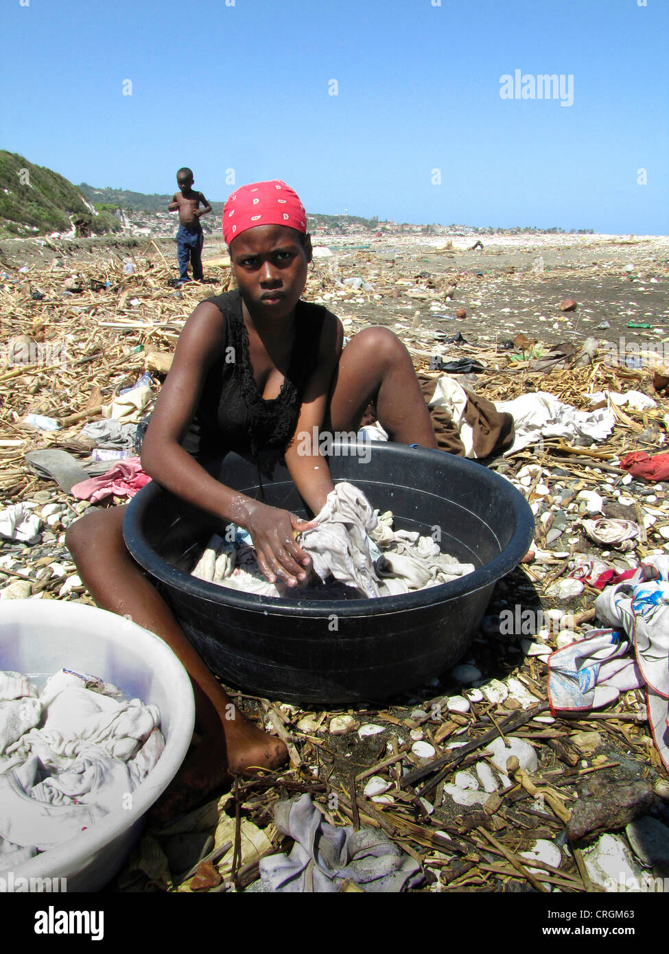 woman doing her laundry in a plastic bowl at a beach full of flotsam, small boy walking in the background, Haiti, - Stock Image