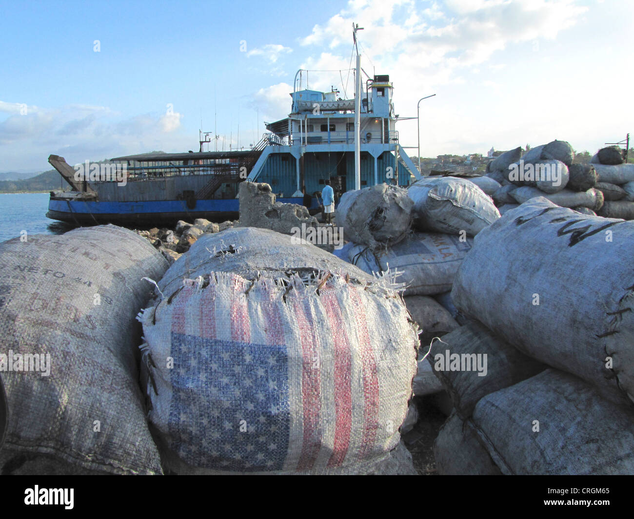piled bags of charcoal, some with US flag on them, in the port of J�r�mie, ferry in the background, Haiti, Grande - Stock Image
