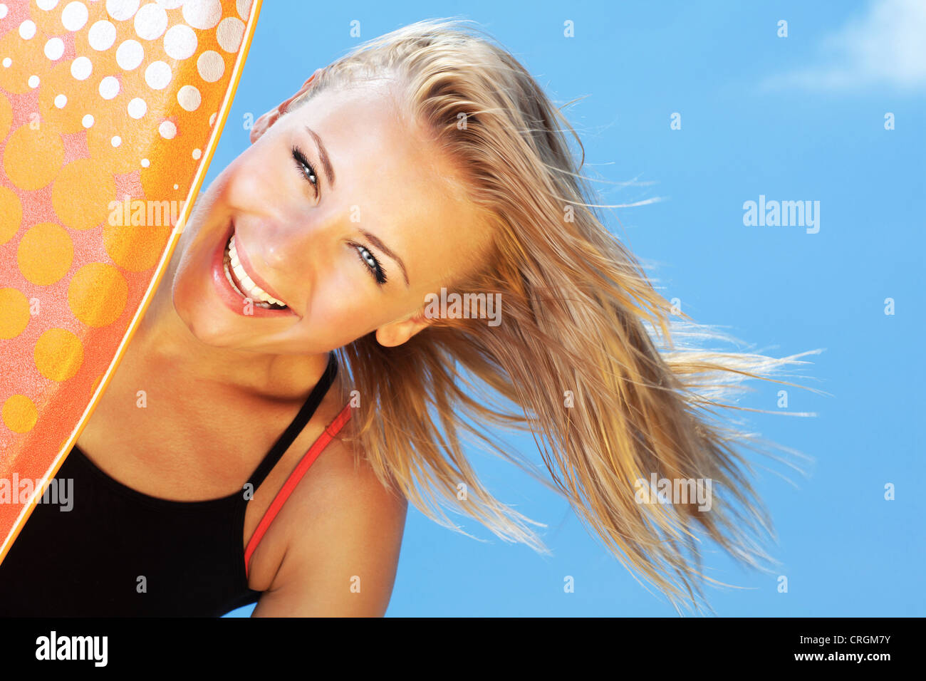 Happy surfer beautiful teen girl laughing, pretty female holds bodyboard, young healthy woman playing surf sport - Stock Image