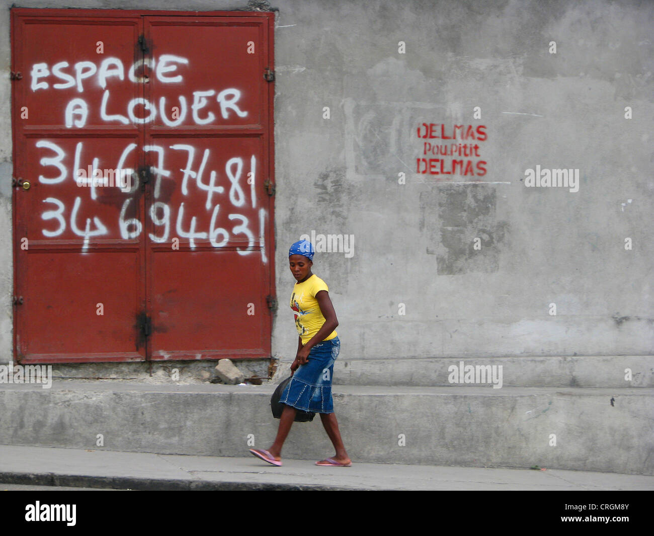 woman walking along a concrete wall with an iron door offering space for rent, Haiti, Province de l'Ouest, Delmas, - Stock Image