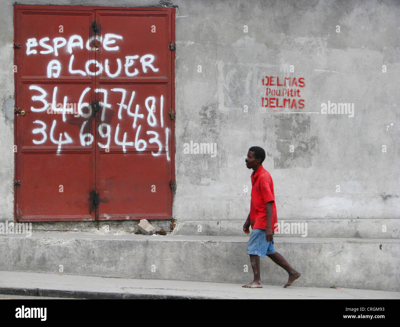 man walking along a concrete wall with an iron door offering space for rent, Haiti, Province de l'Ouest, Delmas, - Stock Image