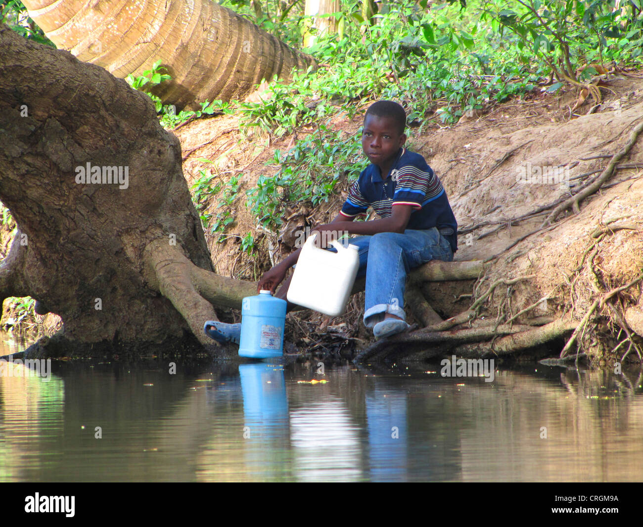 boy fetching water from a river with canister, Haiti, Grande Anse, Abricots - Stock Image
