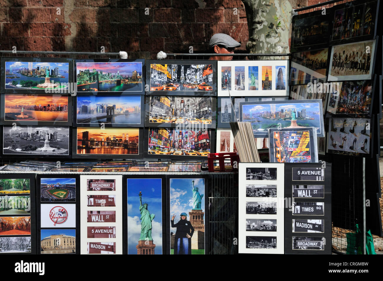 A man stands behind a large display of photos, signs and other souvenirs of New York at Battery Park - Stock Image
