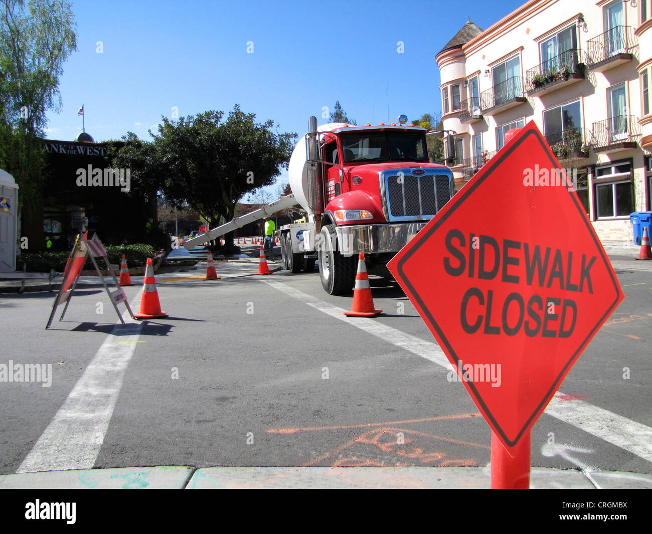 Traffic sign displaying temporary closure of side walk at construction site, cement mixer in the background, USA, - Stock Image