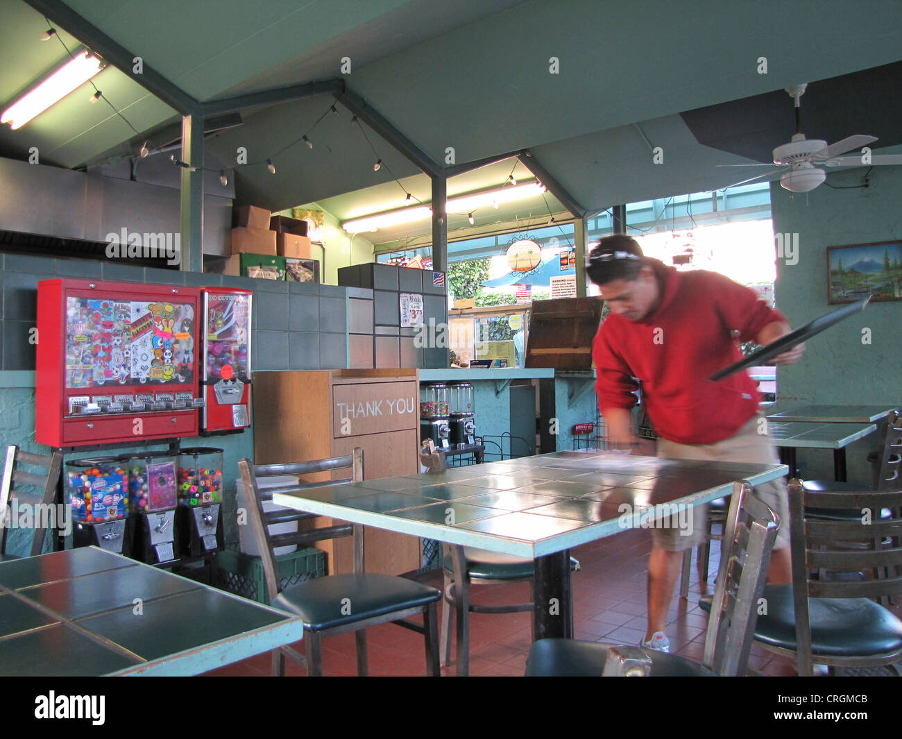 Man cleaning table in American fast food restaurant, chewing-gum machine in the left of the image, USA, California, - Stock Image