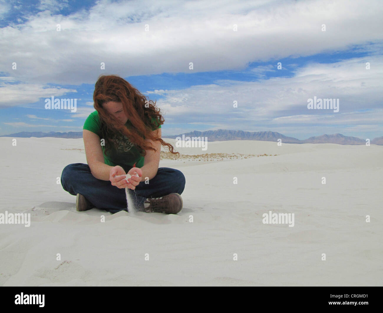Young redheaded woman let white sand running throught her fingers, USA, New Mexico, White Sands National Monument, - Stock Image