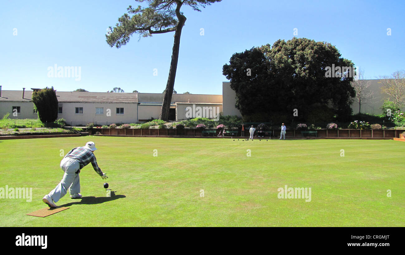 Man playing boules on a well-kept green hayfield, USA, California, San Francisco - Stock Image