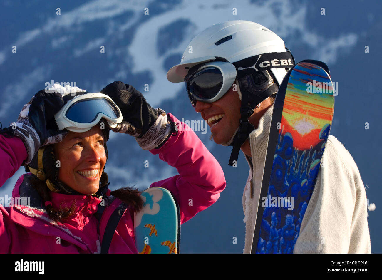 couple with skis, helmets and ski goggles in the Alps, France - Stock Image