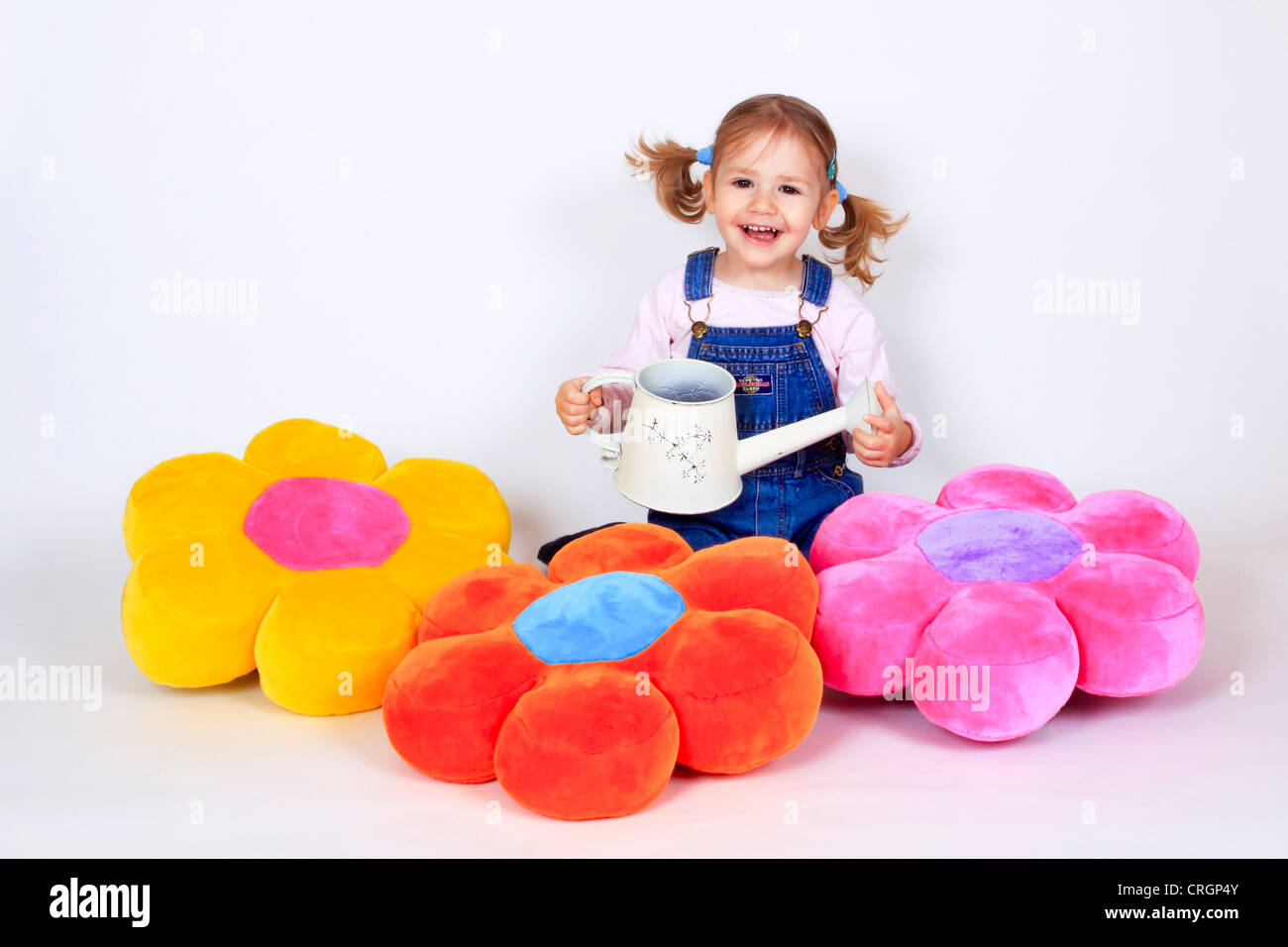 little girl waters flower pillows with watering can Stock Photo