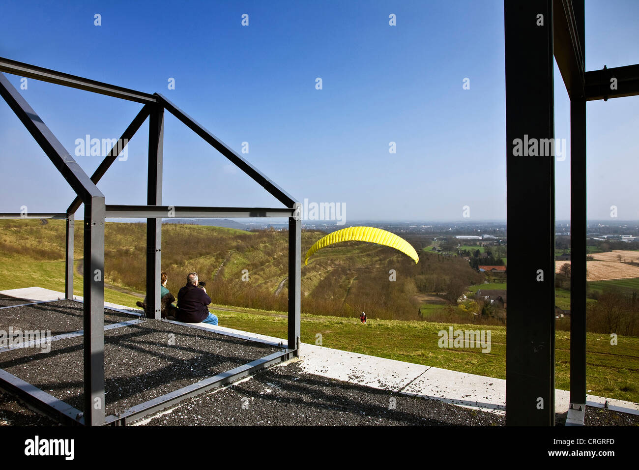 two people watching a Paraglider starting on Norddeutschland stockpile, Germany, North Rhine-Westphalia, Neukirchen - Stock Image