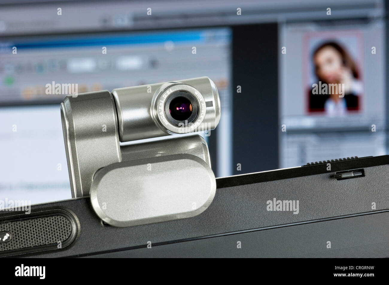 webcam installed on computer monitor, screenshot with portrait of a woman in the background - Stock Image
