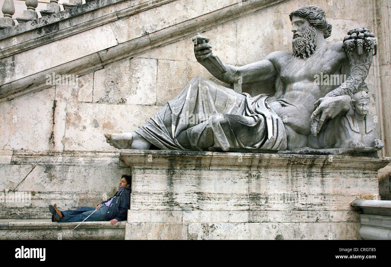 sleeping man leaning at a statue of Jupiter in a corresponding pose, Italy, Rome - Stock Image