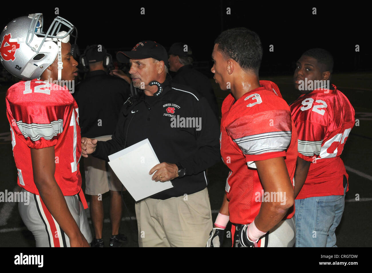 Coach giving instructions to his quarterback at a high school game in Glen Burnie, Maryland - Stock Image