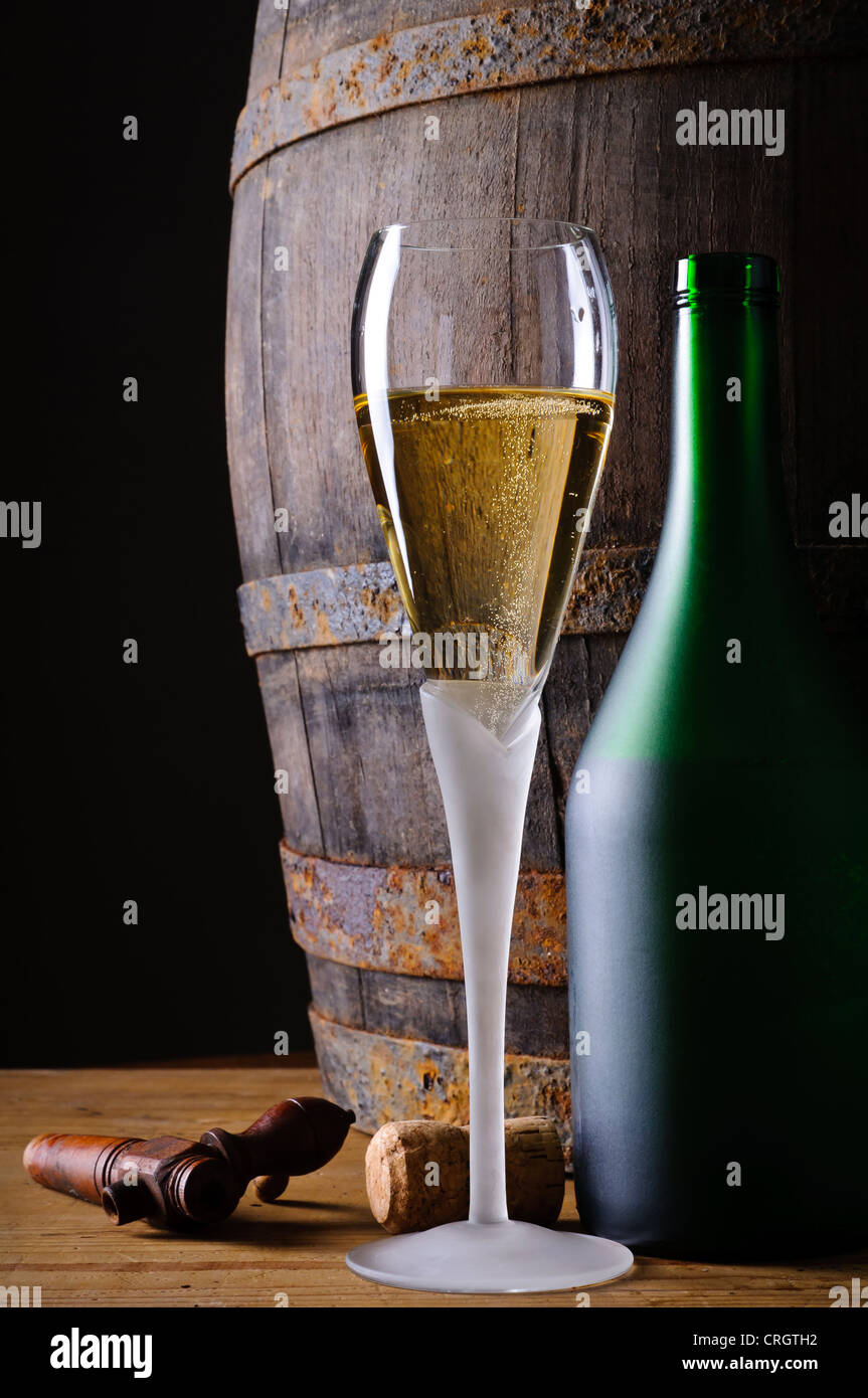Still life with glass and bottle of champagne or prosecco in cellar with wooden barrel - Stock Image
