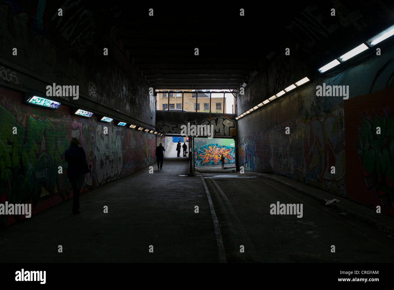 Sinister silhouettes in underpass tunnel with walls covered with urban graffiti. - Stock Image