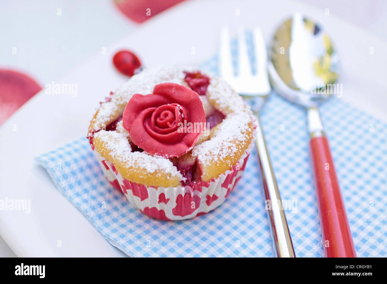 Muffin with marchpane rose on coffee table - Stock Image