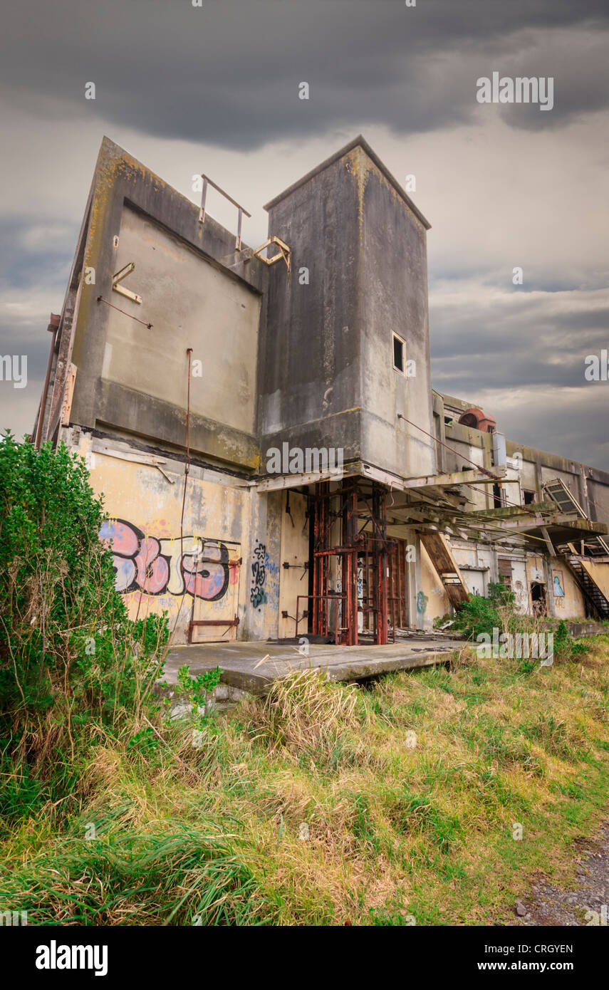 The ruins of an old factory, abandoned to the elements. - Stock Image