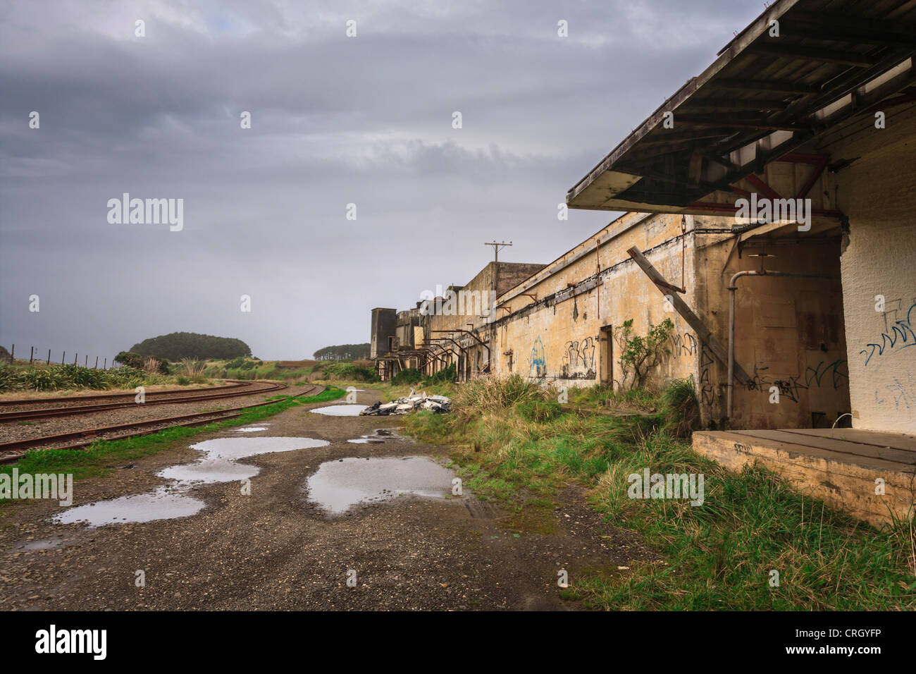 Abandoned factory on a wet day, gray sky, puddles on the ground, graffiti. Stock Photo