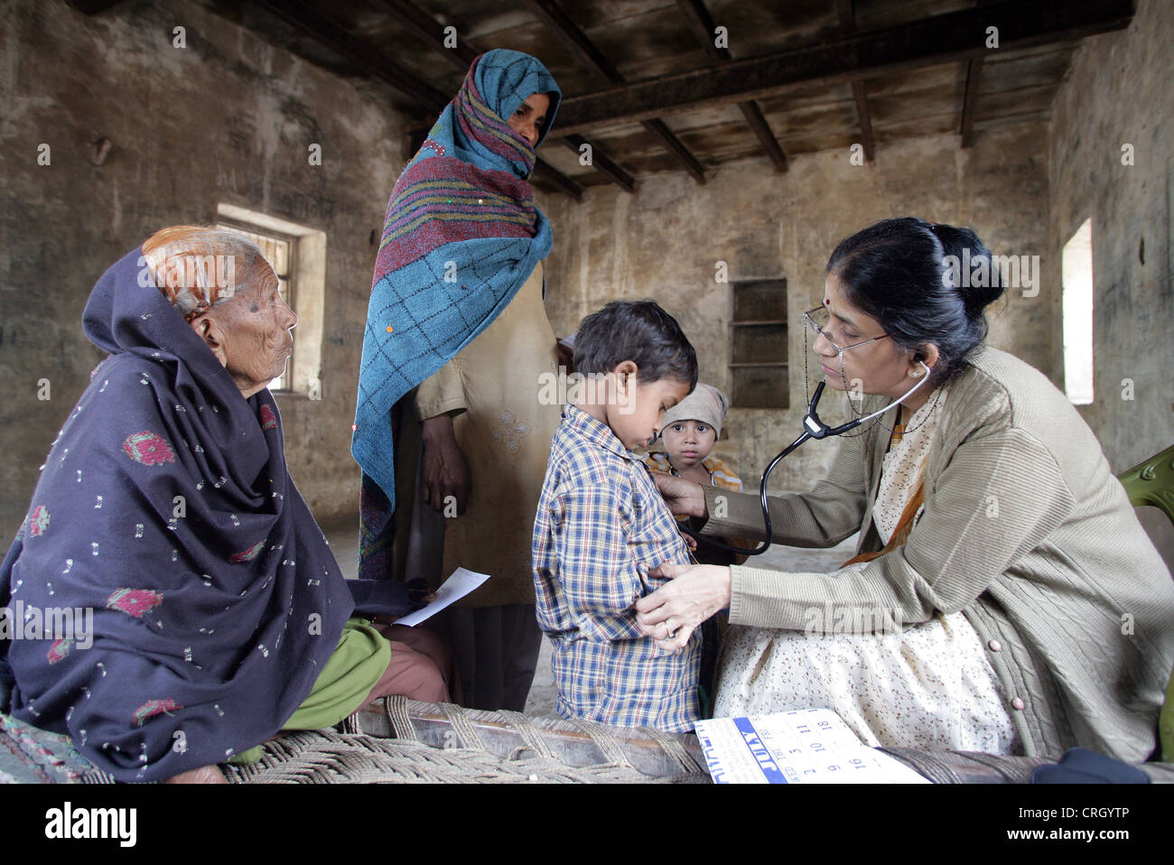 Volunteer Doctor (right) examines sick inhabitants of a village in India without any fee/royalty - Stock Image