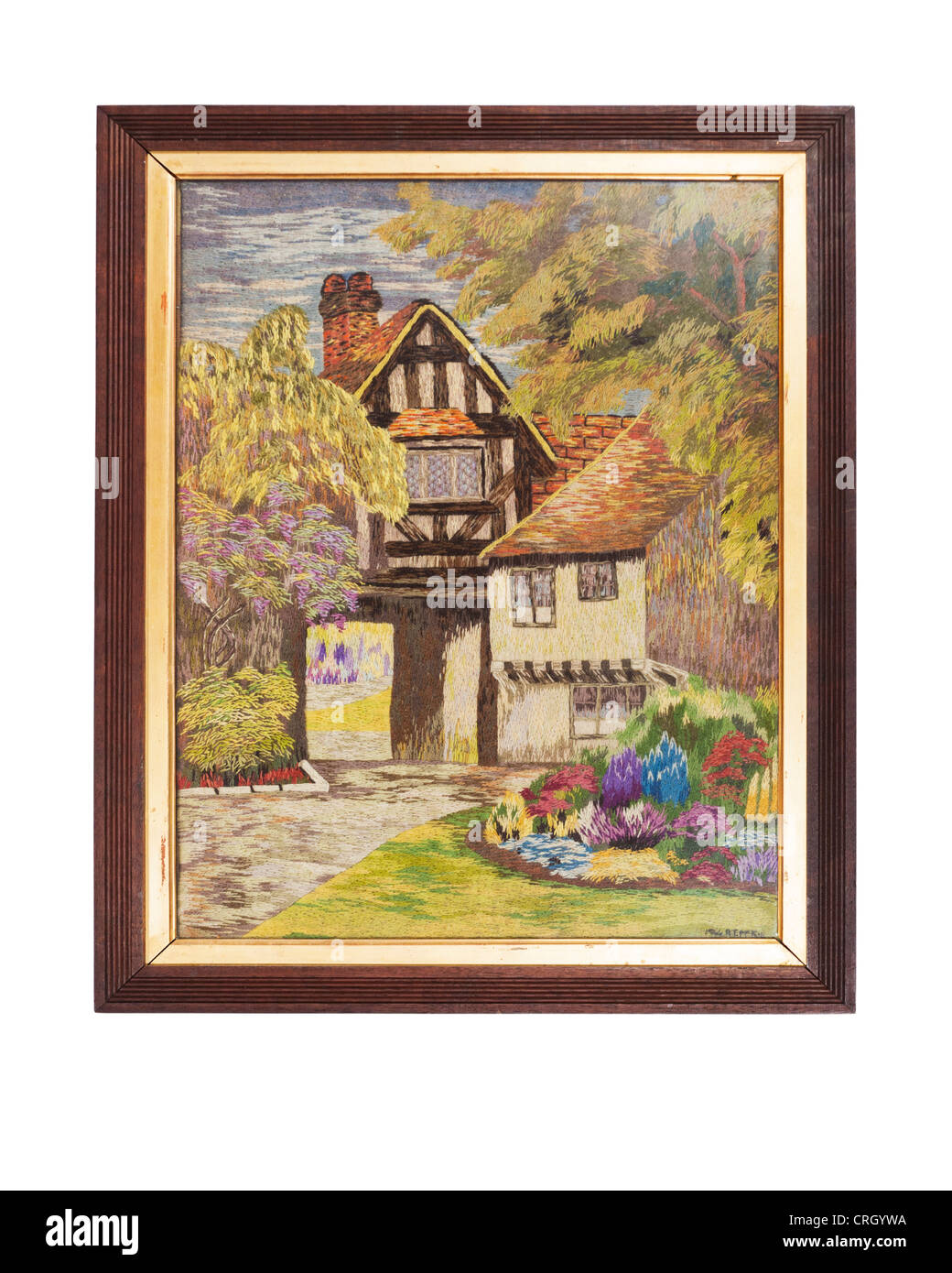 Framed hand embroidered picture of tudor cittage and country garden, done during the years of WW2. - Stock Image