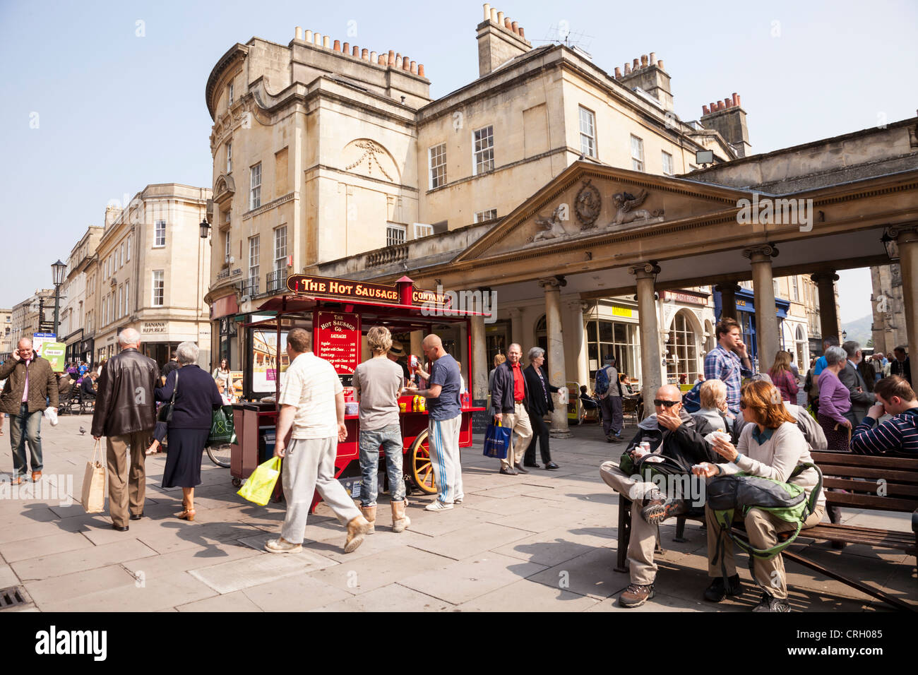 One of the Hot Sausage Company's stalls in the centre of Bath, Somerset, England, surrounded by people. - Stock Image