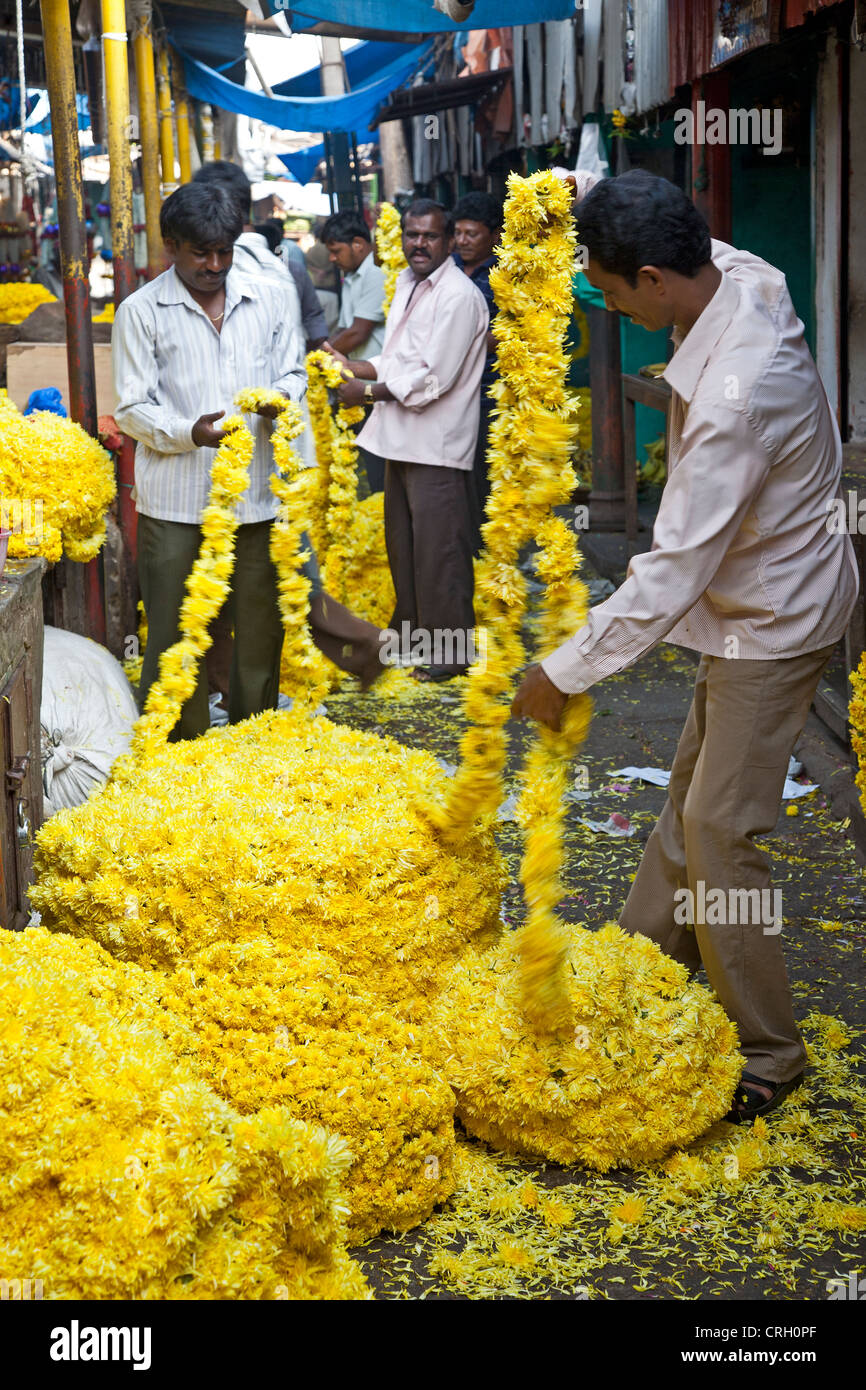 Men piling flower garlands. Devaraja Flower market. Mysore. India - Stock Image