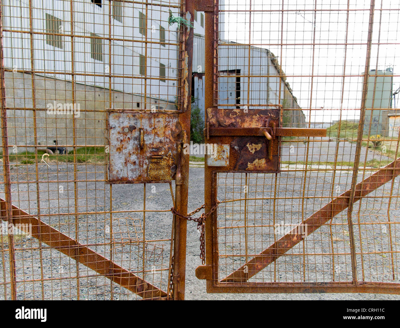 Rusted gates of a derelict run down factory closed down in Ireland - Stock Image