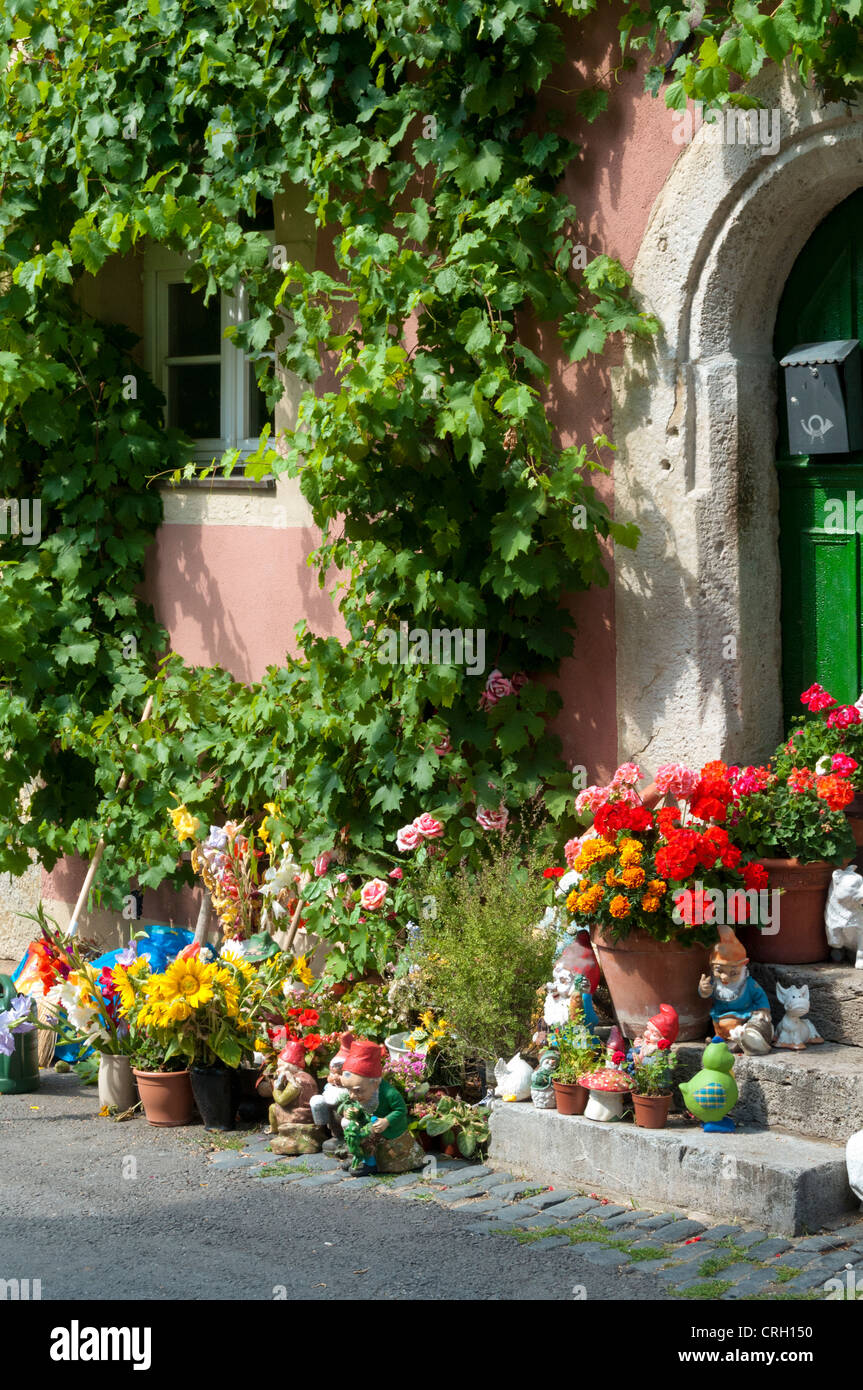 Flowers, pot plants and garden gnomes outside a house in a village in Germany - Stock Image