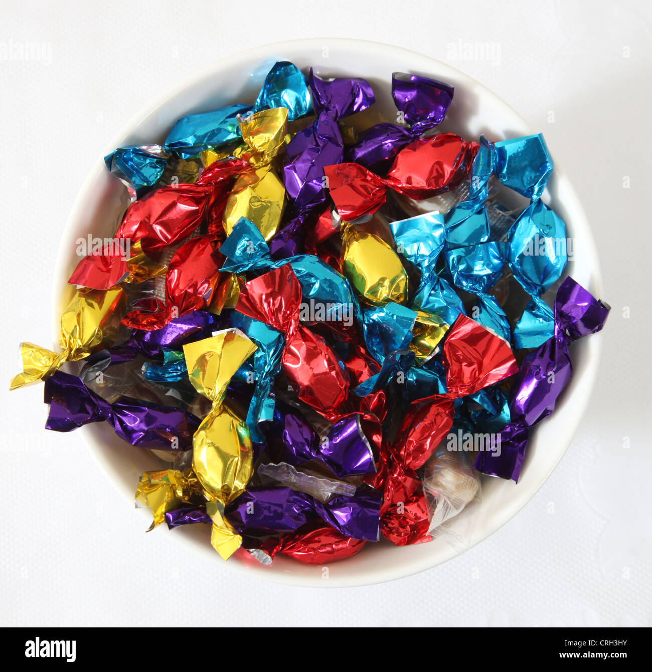 A bowl of sweets in colourful wrappers. - Stock Image