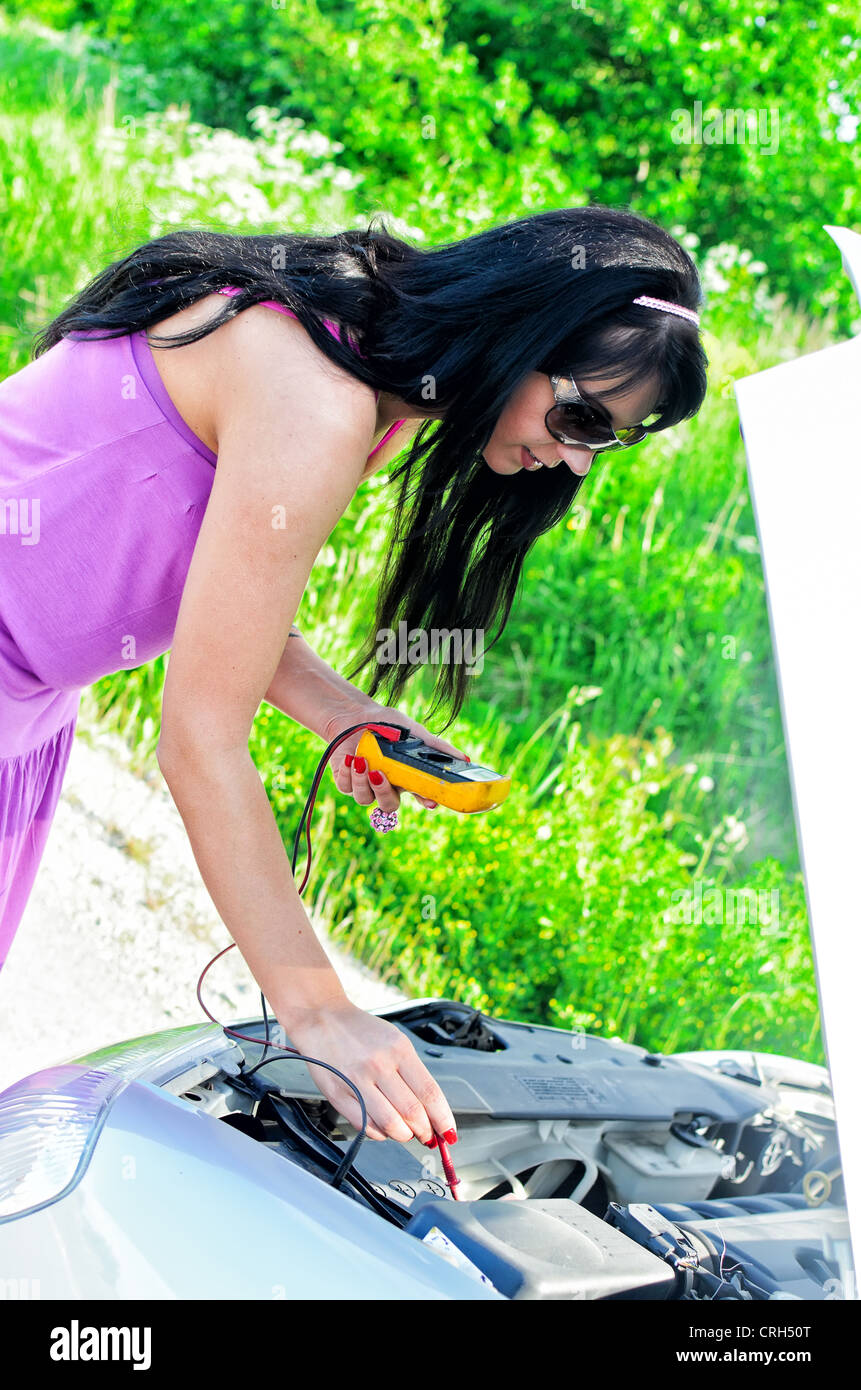 Woman controls lead–acid battery charge with voltmeter - Stock Image