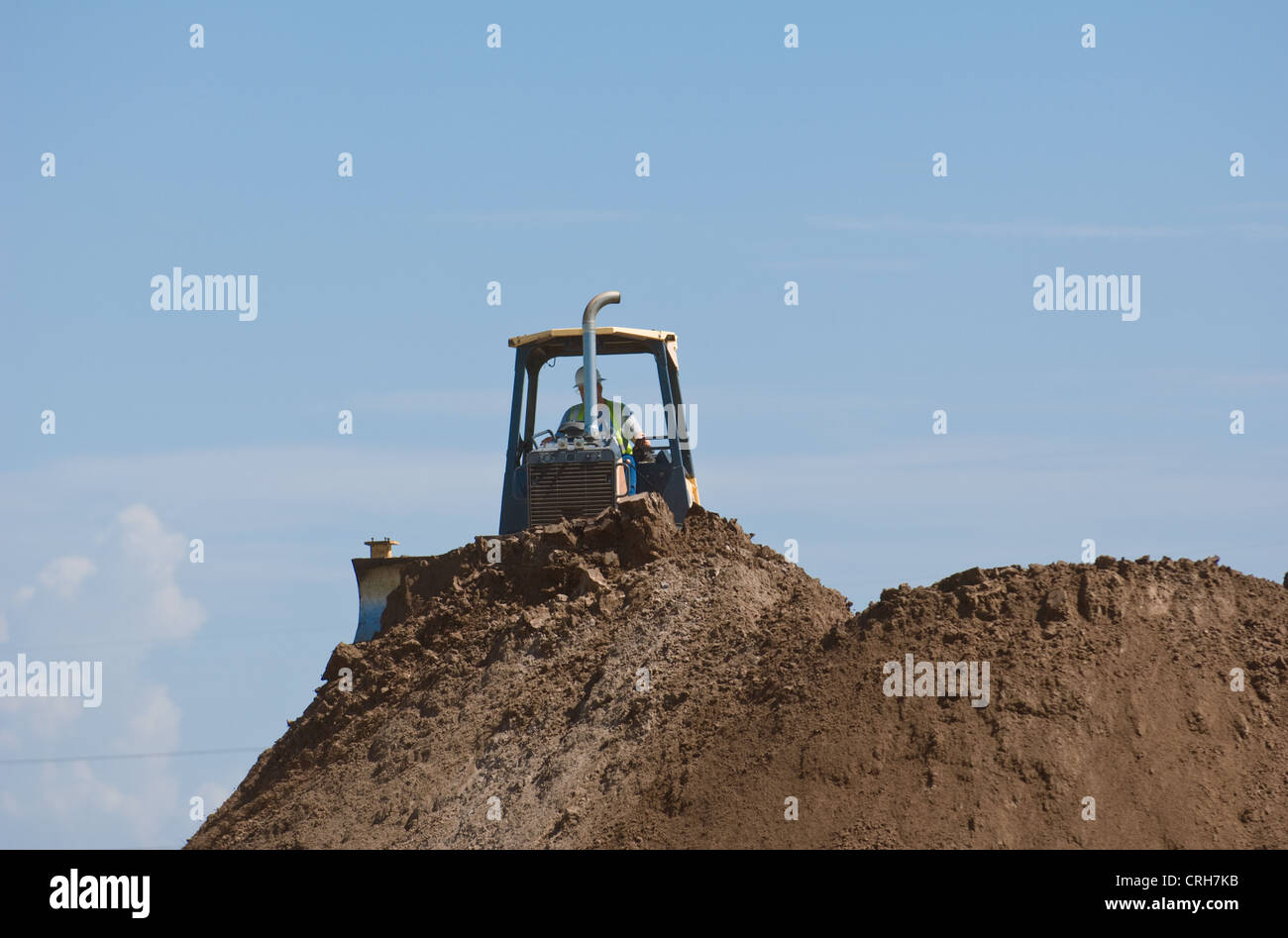 Bulldozer on top of dirt pile at construction site - Stock Image
